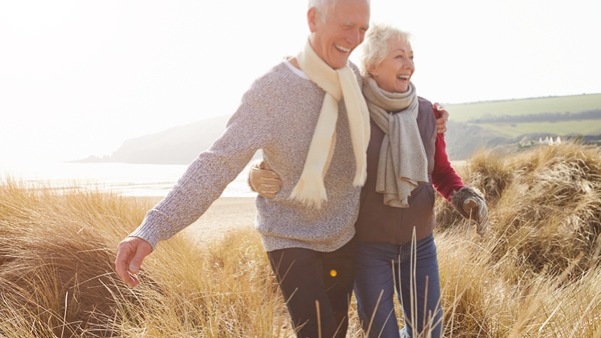 Senior Couple Walking Through Sand Dunes On Winter Beach Smiling